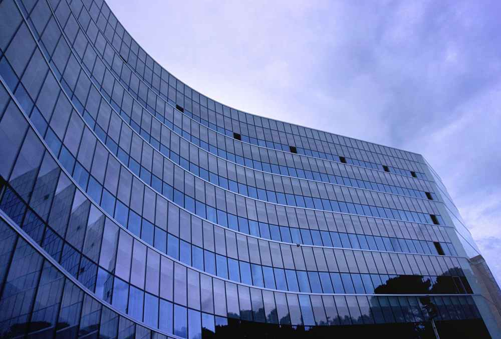 fish eye view photo of glass high story building over white cloudy sky during daytime